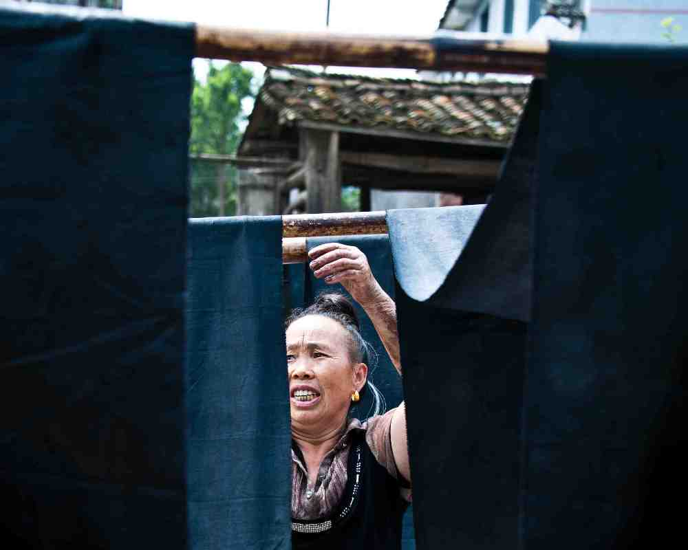 Miao woman hanging indigo fabric