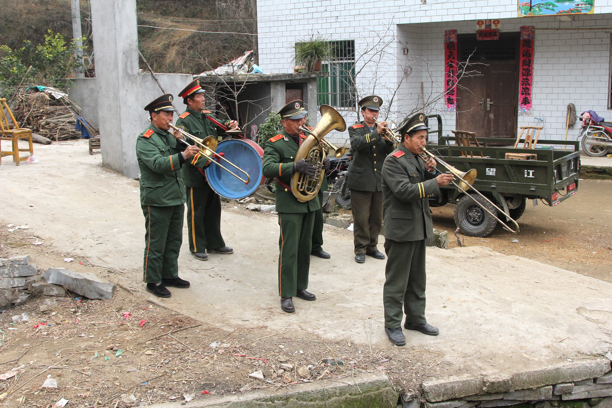 Frank: A band made up of farmers wearing People's Liberation Army uniforms greeted Rocky and Xiao Piao after they arrived in the village for their wedding in a black BMW. I drove guests in my rented Buick van.